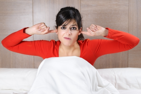 bother: Beautiful brunette caucasian woman covering her ears with her fingers and showing his displeasure. Hispanic model in bed. Stock Photo