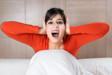 Brunette young caucasian woman covering her ears with her hands and screaming with open mouth. Hispanic model in bed.