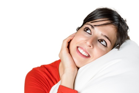 Isolated cute brunette woman portrait. Hispanic model smiling, relaxing and day dreaming with head in pillow and hand touching her face. Stock Photo - 16732543