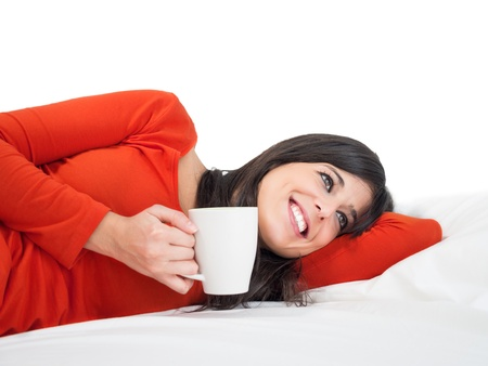 peacefulness: Relaxed and peaceful young woman lying in bed and enjoy a cup of coffee. Tranquility and peacefulness at home.
