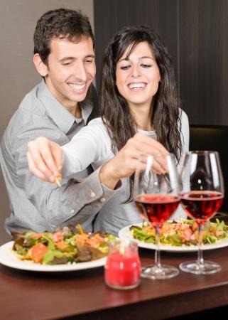 diner romantique: Jeune couple sur la date d'anniversaire. Jeune homme et femme souriant et la cuisine ensemble, la préparation d'un dîner romantique. Banque d'images