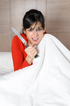 rancor: Frightened woman covering with the sheet on the bed and holding a knife in her hand. Brunette model looking scared and disturbed in bedroom.