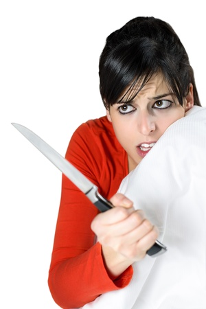 Frightened woman covering with the sheet on the bed and holding a knife in her hand. Brunette model looking scared and threatening isolated.