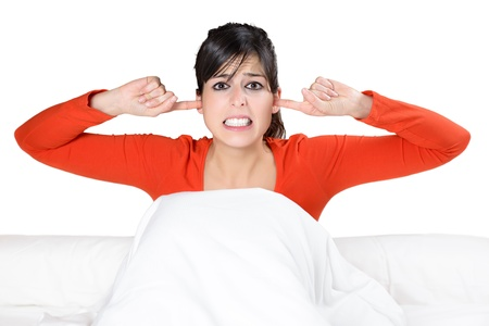 bother: Beautiful brunette caucasian woman covering her ears with her fingers and showing his displeasure. Hispanic model in bed isolated.