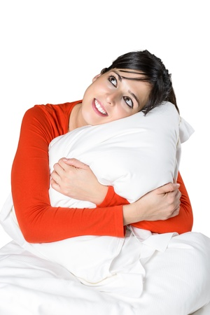 Isolated cute brunette woman hugging a pillow. Hispanic model smiling, relaxing and day dreaming in bed. Stock Photo - 16825996
