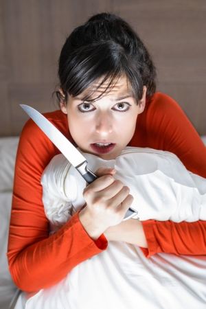 Young girl frightened and alone at home holding a knife. Scared caucasian model sitting on bed at night. photo