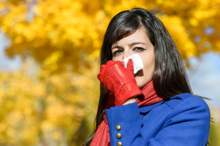 catarrh: Woman with flu blowing her nose with a kleenex on a cold autumn day.