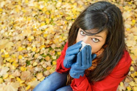 Sad woman with flu blowing her nose with a tissue on a cold day. Caucasian model lying sitting outside on autumn golden leaves. photo
