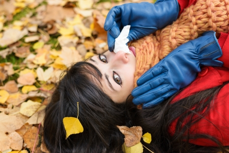 catarrh: Sad woman with flu blowing her nose with a tissue on a cold day. Caucasian model lying down on autumn golden leaves.