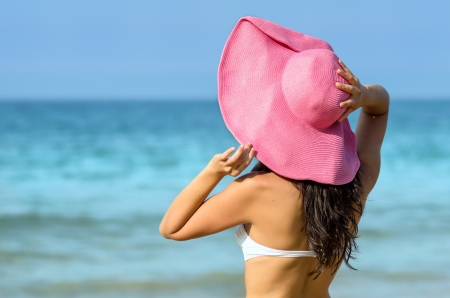 pink hat: Young woman enjoying the sun in a summer day in the beach. Model wearing pink pamela hat and white bikini towards the sea.
