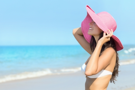 pink hat: Cheerful sexy woman enjoying the sun in a summer day  in the beach. Model with pink pamela hat and white bikini standing towards the sea.