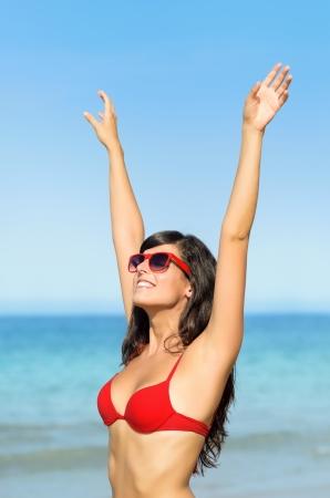 Jeune femme sexy en bikini rouge souriant et en levant les bras vers le san à la plage. Brunette modèle bronzé, lunettes de soleil sur fond de mer bleue.