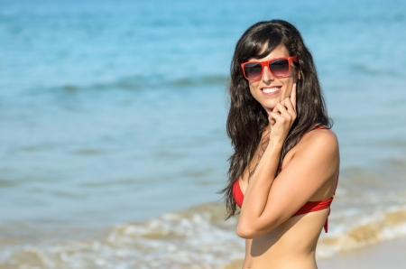 Happy young sexy woman in beach smiling  Caucasian hispanic model with red sunglasses and bikini on blue sea background Stock Photo - 17133547