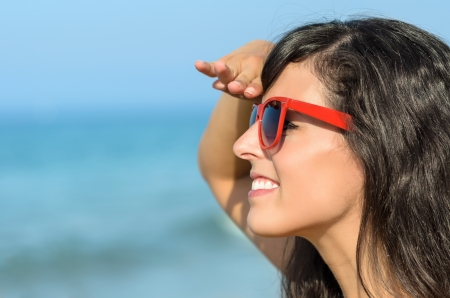 Woman on the beach watching and smiling with blue sea in the background  Caucasian model with red sunglasses looking like life guard  Stock Photo - 17133519