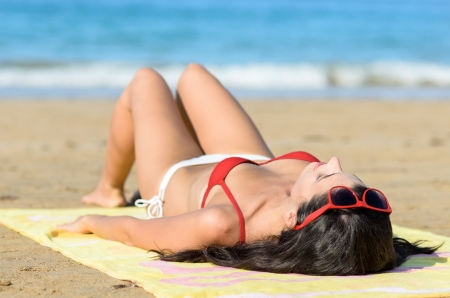 lying down: Happiness on the beach at summer. Young sexy woman lying down, sunbathing and resting towards the sea.