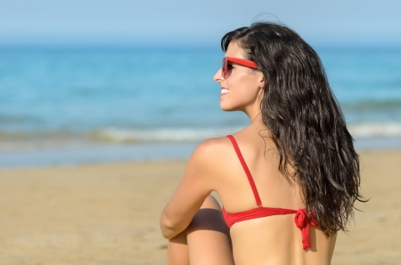 Beautiful brunette young woman sitting on the beach and watching the blue sea. Caucasian beautiful model wearing red bikini and sunglasses. photo