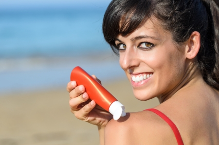 Happy young woman applying suntan lotion in her shoulder for sunbathing in the beach at summer in a sunny day. photo