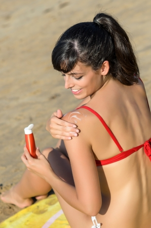 skin protection: Young woman applying suntan lotion in her shoulder for sunbathing in the beach at summer in a sunny day. Stock Photo
