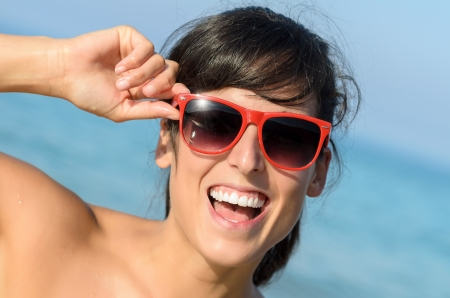 Playful beautiful young woman with happy facial expression in a summer day on the beach. Caucasian pretty brunette with red sunglasses and blue sea on background Stock Photo - 17317323
