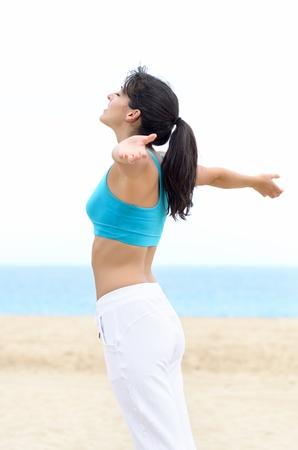 aire puro: Mujer joven con los brazos levantados extendidos, sintiendo la brisa y el aire fresco para respirar. Libertad concepto de verano en la playa. Foto de archivo