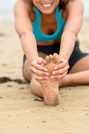 grabbing: Female hands grabbing up foot sole and stretching leg  Unrecognizable young woman exercising on beach