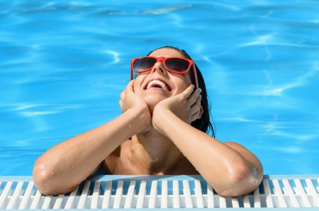 Happy smiling woman in swimming pool  Caucasian girl portrait with sunglasses  Model enjoying water, sun and summer  photo