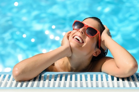 Portrait of beautiful woman face with red sunglasses in swimming pool  Pleaseure moment in spa resort on hot summer day  Blue bokeh water background
