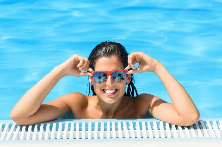 sunglasses reflection: Wet young beautiful happy woman in fresh swimming pool  Girl face happiness expression with red sunglasses on summer hot day  Tropical resort scene reflection in glasses  Stock Photo
