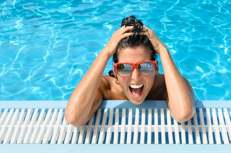 Young beautiful crazy woman in fresh swimming pool of resort  Funny happy girl face expression with red sunglasses on summer hot day  Reflection of beach and palms in glasses  photo