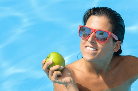 Woman holding an apple in a swimming pool on summer  Diet and temptation concept with caucasian brunette model  Stock Photo - 17482614
