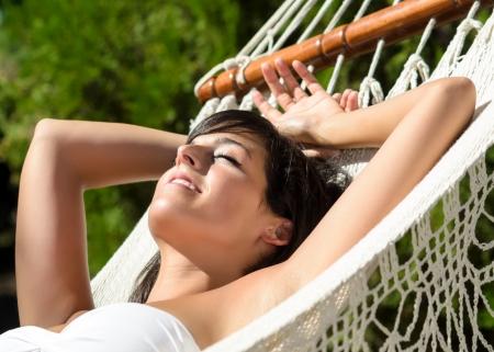 hamaca: La mujer se relaja y se acuesta en la hamaca para la siesta Paz relajarse en el jard�n de verano