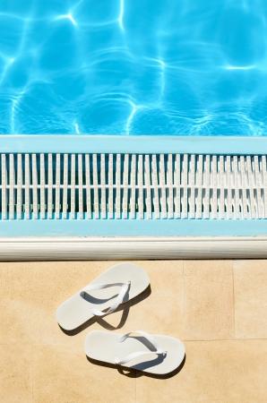 sandalias: Summer concepto con chanclas blancas junto a la piscina en el día soleado y el agua azul