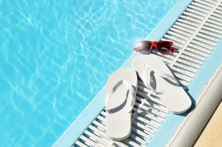 sandalias: Concepto verano caliente con chanclas y gafas de sol blancas rojas en Reflexión de Sun junto a la piscina con gafas