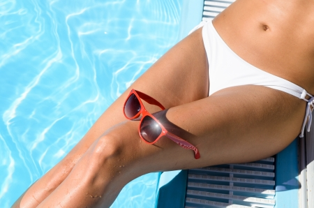 Female sexy tanned wet legs into water at pool  Red sunglasses on the knee Stock Photo - 17482781
