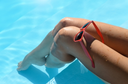 Female sexy tanned wet legs into water at pool  Red sunglasses on the knee Stock Photo - 17482616