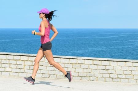 actief luisteren: Fitness meisje loopt snel op zomerdag met uitzicht op zee op de achtergrond. Mooie vrouwelijke atleet uitoefening van het dragen van sport cap.