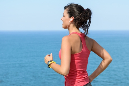 Woman running with earphones on sea background. Caucasian beautiful fitness girl working out on summer. Copyspace. photo
