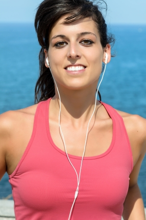 Woman running portrait on sea background. Beautiful fitness caucasian girl jogging on summer photo