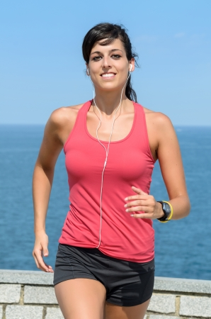 Happy woman running on summer. Female caucasian fitness athlete jogging on sea background. photo