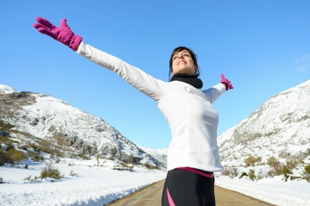 bliss: Running woman success bliss sport concept on winter road mountain background  Beautiful cheerful caucasian Female athlete with arms up