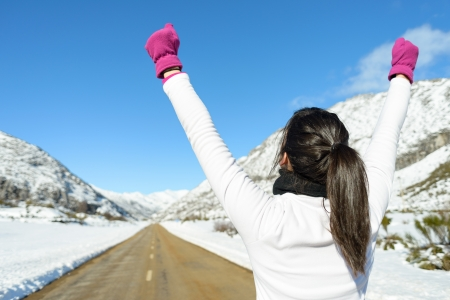 Running woman success sport concept on winter road mountain background  Sportswoman winning on snowy landscape  photo