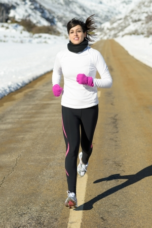 Winter running woman on mountain road. Caucasian female athlete with warm sport clothes exercising in snowy landscape. photo