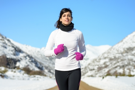Woman running on winter mountain portrait. Caucasian beautiful female athlete exercising on sunny cold day. Sportswoman with warm sport clothes.