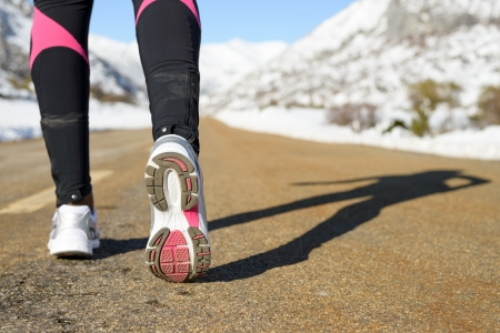 Winter exercising and run concept on mountain road. Female runner shadow and sport footwear.  Copy space