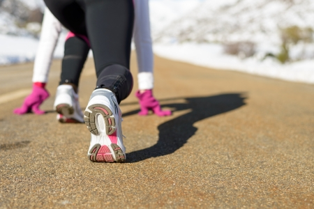 runing: Sportswoman runing on winter concept. Female athlete ready to run on mountain snowy road. Copy space.