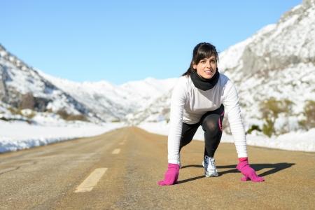 Woman running on winter mountain road. Caucasian female athlete ready to run on snow landscape. photo