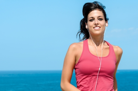 Happy woman running on summer on sea background  Female caucasian fitness athlete jogging  photo