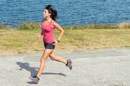 Female athlete running on summer  Female caucasian fitness woman jogging on sea background  photo