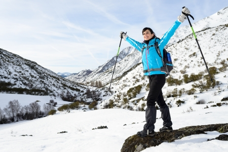 Happy woman hiking on winter snowy mountain trip with arms up.  Successful hiker travel achievement. photo