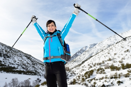 Winner woman hiking success on winter snowy mountains landscape. Winter vacations trip on nature. photo